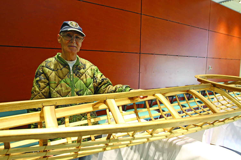 Vince Pikonganna stands behind the kayak.