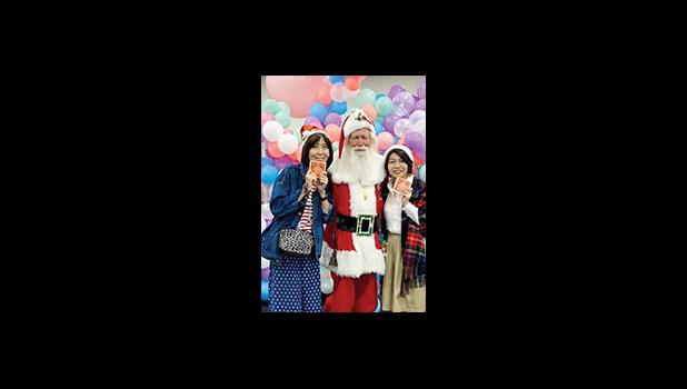 Santa Paul poses with two fans during his visit to the 2019 World Santa Claus Congress in Japan.