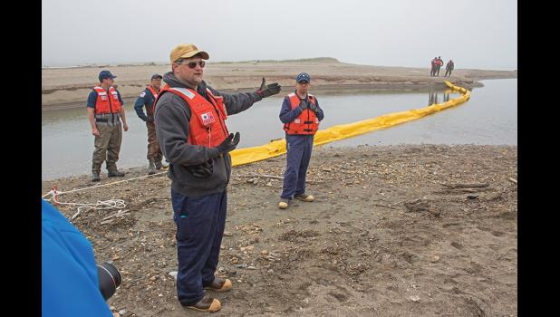 BOOM DEPLOYMENT— Matt Odum, left, and James Nunez, center, of the USCG led the deployment of an oil containment boom at Hastings Creek on Wednesday, June 15.