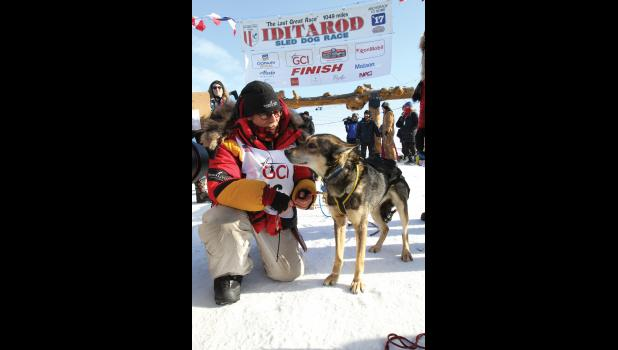 WE DID IT— Mitch Seavey of Sterling, Alaska, and his lead dog have a moment after