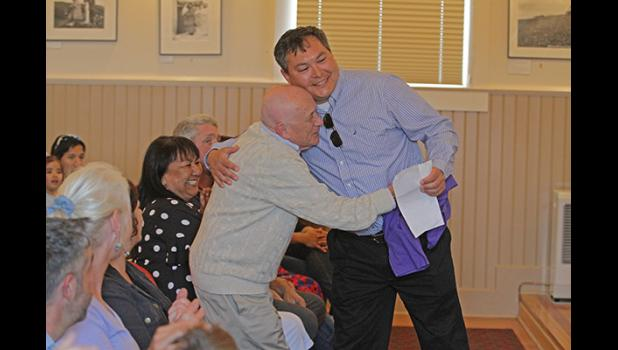 Richard Beneville gives Jake Kenick a hug during a celebration of Beneville's contributions to Nome last year at Old St. Joe's.