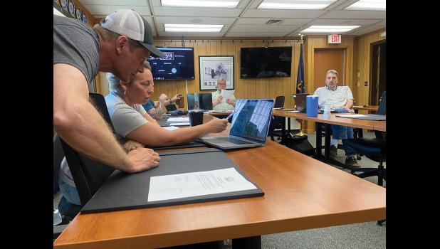 MINING PERMIT— Councilwoman Jennifer Reader confirms with Shawn Pomrenke of Northwest Gold Diggers where he plans to mine for gold within the Moonlight Wells Protective area, during Tuesday's Nome Common Council meeting.