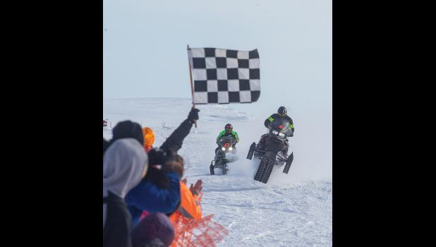 CLOSE FINISH – Riders Steven Quincy Williamson, bib 47— winner of the B class—  races Jacob Hannon, sixth place finisher in the C class, to the finish line at the Nome-Golovin 200 race held last Saturday.