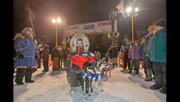 K300 CHAMP— Pete Kaiser poses with his lead dogs under the Kuskokwim 300 finish line arch in Bethel after winning for the fifth time the prestigious mid-distance sled dog race on Sunday morning.