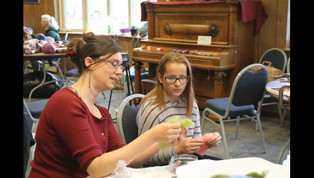 Amy Jamgochian shows Iryna Kadatska how to prepare fiber for needle felting.