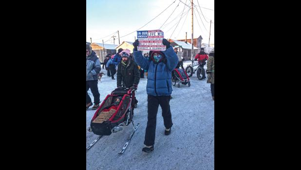 RESPECT AND DIVERSITY— Carol Gales holds up a sign calling for respect while celebrating diversity during the march in Nome.