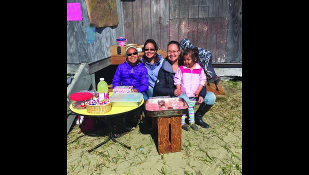 LEMONADE DAY IN SHISHMAREF— Bella, Wilsa and Irene Ahgupuk and Courtney Nayokpuk sit next to their lemonade stand in Shishmaref. Photo by Annie Weyiouanna. See more lemonade day photos at our Image Gallery.