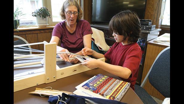 Kirsten Bey helps out Samuel Norris on the loom.
