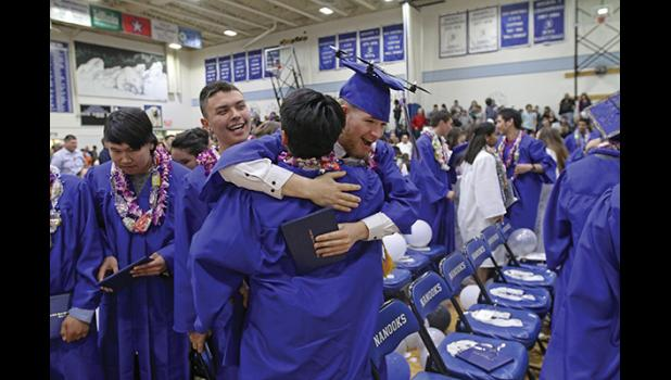 WE DID IT—2019 Nome-Beltz extension program graduate Aaron Motis hugs Nome-Beltz graduate Ethan Ahkvaluk as Jeffrey Saclamana Jr. smiles on, shortly after they officially graduated from high school last Wednesday.
