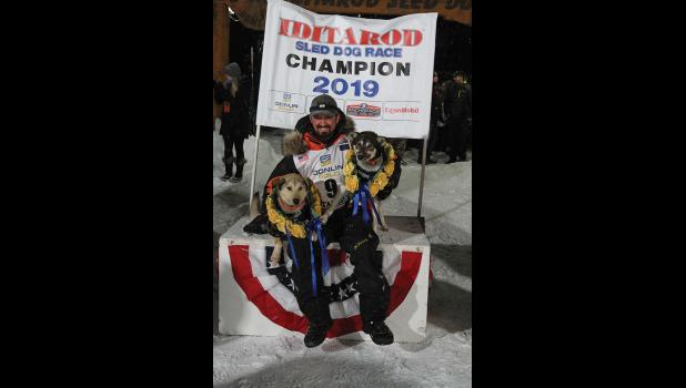 Iditarod champion Pete Kaiser claims the throne with his lead dogs Morrow and Lucy.