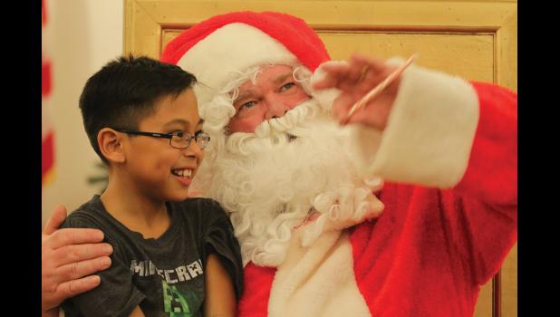 SEE THE REINDEER FLY?— Santa explained to young Trevor White whence he came and assured him that he will take all Christmas present wishes of Nome kids' to his elves. Santa made a special appearance at the City's Christmas Extravaganza on Dec. 6, at Old St. Joe's.