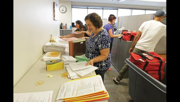 PREPARATIONS— Div. of Elections Supervisor Angelique Horton, center, and her crew Monica Giang, Katie O'Connor and Alec Johnson on Friday, July 29 prepared bags with election materials for shipping.