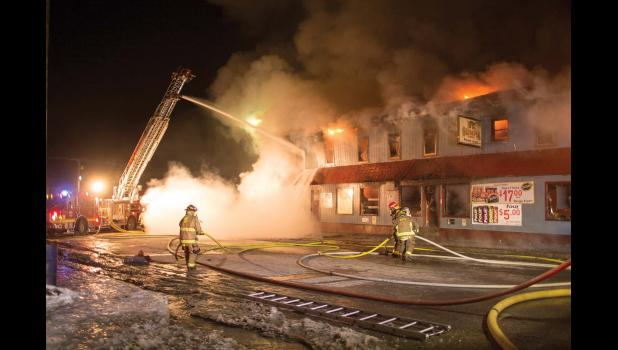 FIRE AT THE POLARIS— Nome Volunteer Fire Dept. fire fighter Kevin Knowlton walks by the burning Polaris building in the early morning of Oct. 31. Later that afternoon, one person's body was recovered from the burned rubble of the back building. The identification is pending