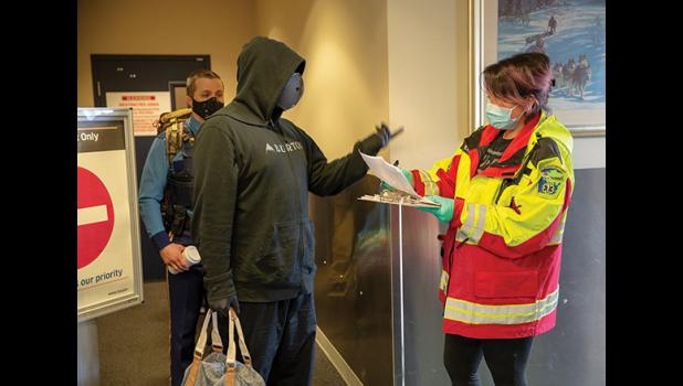 ARRIVAL IN NOME – Nome Emergency Services Technician Rose Reale checks an arrival's travel permit in the Alaska Airlines terminal in Nome on Thursday