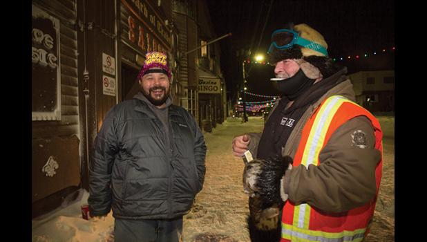 SAFETY PATROL— Arnold Mueller, left, and safety patroller Chuck Titus enjoy a laugh in front of the Board of Trade Saloon on New Year's Eve.
